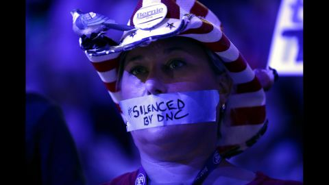 """Tape on a delegate's mouth makes a statement Monday about the Democratic National Committee. Recently leaked committee emails <a href=""""http://www.cnn.com/2016/07/22/politics/dnc-wikileaks-emails/index.html"""" target=""""_blank"""">appeared to show favoritism toward Clinton</a> in the primary race, and many Sanders supporters entered the convention upset. The controversy has caused Debbie Wasserman Schultz to step down as the committee's chairwoman at the end of the convention."""