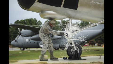 Air Force Master Sgt. Matthew Tabor breaks a bottle to christen an H-21B helicopter at the Little Rock Air Force Base in Arkansas on Thursday, July 14.