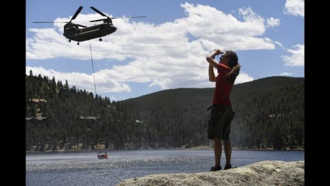 Adam Jones, a resident of Nederland, Colorado, takes pictures as an Army helicopter collects water from the Barker Dam to fight the Cold Springs Fire on Sunday, July 10.