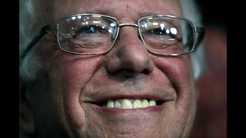 Sanders smiles while attending roll call. He moved to name Clinton the official nominee.