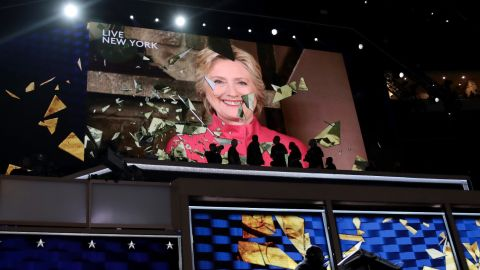 """Clinton appears live on a video screen Tuesday night. Just a few hours earlier, she officially became the party's presidential nominee. She is the first woman to lead a major party's presidential ticket. """"I can't believe we just put the biggest crack in that glass ceiling yet,"""" she told the crowd."""