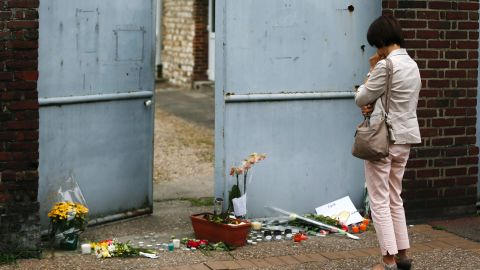 A woman mourns in front of the house of Father Jacques Hamel on July 27, 2016 in Saint-Etienne-du-Rouvray, where the priest was killed the day before in the latest of a string of attacks against Western targets claimed by or blamed on the Islamic State jihadist group.