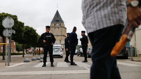 A man carries a French baguette as police officers stand guard the Saint-Etienne church.