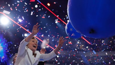 US Democratic Presidential Candidate Hillary Clinton reaches for ballooons on the final day of the 2016 Democratic National Convention on July 28, 2016, at the Wells Fargo Center in Philadelphia, Pennsylvania.