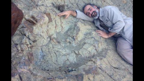 Paleontologist Sebastian Apesteguia lies next to a newly discovered dinosaur footprint in Bolivia.
