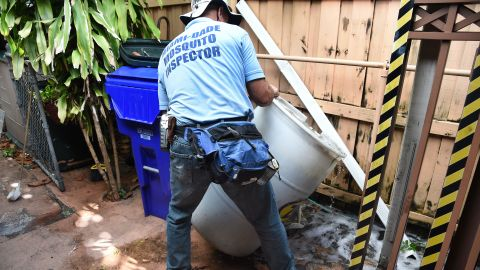 """Miami-Dade mosquito control worker Carlos Vargas dumps a barrel of standing water that can incubate the Aedes aegypti mosquito larvae at a home in Miami, Florida, on June 08, 2016.  Of the forty different types of mosquito found in Miami -Dade the Aedes aegypti mosquito or yellow fever mosquito is responsible for transmitting diseases such as the Zika Virus.  / AFP / RHONA WISE / TO GO WITH AFP STORY by Leila MACOR, """"Florida health warriors deploy in war on Zika""""        (Photo credit should read RHONA WISE/AFP/Getty Images)"""