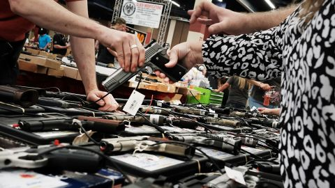 A woman tries a pistol at a gun show where thousands of different weapons are displayed for sale on July 10, 2016 in Fort Worth, Texas.