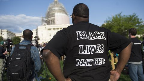 """A man wears a """"Black Lives Matter"""" t-shirt as he demonstrates along with the group Justice League NYC and others participate in a March2Justice rally for criminal justice reform legislation to end racial profiling and demilitarize police forces outside the US Capitol in Washington, DC, April 21, 2015. Some members of the group spent a week traveling from New York City to Washington, ending with a protest rally on the National Mall. AFP PHOTO / SAUL LOEB        (Photo credit should read SAUL LOEB/AFP/Getty Images)"""