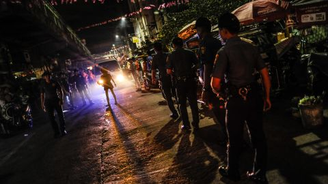 Police patrol a shanty community at night during curfew on June 8, 2016 in Manila. Philippine police have been conducting frequent night raids and revived a curfew for minors that has not been enforced for years.