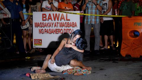 """Jennilyn Olayres hugs her partner, Michael Siaron, on the street where he was shot. Next to him is a placard which reads """"I'm a pusher."""""""