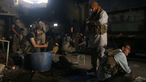 Opposition fighters rest in Aleppo's Ramouseh area as they try to end the Syrian government's seige.