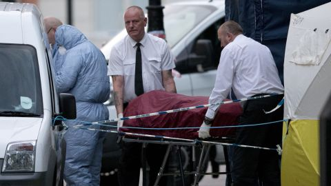 An ambulance crew removes a body from Russell Square early Thursday after a woman was killed.