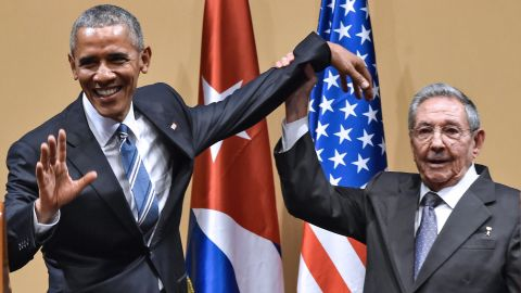 """Cuban President Raul Castro tries to lift up Obama's arm at the end of a joint news conference in Havana, Cuba, in March 2016. Castro hailed Obama's opposition to a long-standing economic """"blockade,"""" but said it would need to end before ties between the two countries are fully normalized."""