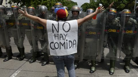 """TOPSHOT - A woman with a sign reading """"There is no food"""" protests against new emergency powers decreed this week by President Nicolas Maduro in front of a line of policemen in Caracas on May 18, 2016.  Public outrage was expected to spill onto the streets of Venezuela Wednesday, with planned nationwide protests marking a new low point in Maduro's unpopular rule. / AFP / FEDERICO PARRA        (Photo credit should read FEDERICO PARRA/AFP/Getty Images)"""