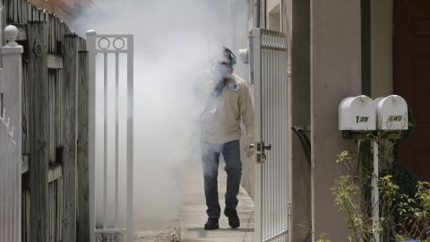 A Miami-Dade County mosquito control worker sprays around a home in the Wynwood area of Miami on Monday, Aug. 1, 2016. The CDC has issued a new advisory that says pregnant women should not travel a Zika-stricken part of Miami, and pregnant women who live there should take steps to prevent mosquito bites and sexual spread of the virus.