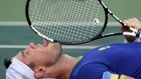 Illya Marchenko, of Ukraine, licks his racquet after losing the match in a tie-breaker during the third set against Andreas Seppi, of Italy.
