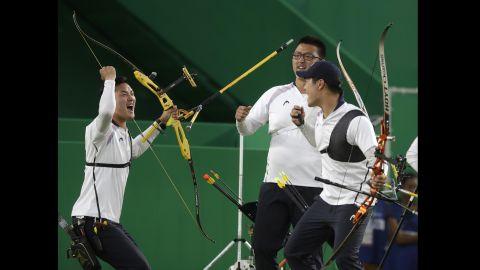 South Korea's Ku Bon-chan, Kim Woo-jin and Lee Seung-yun celebrate after winning the men's team archery gold medal match at the Sambadrome venue.