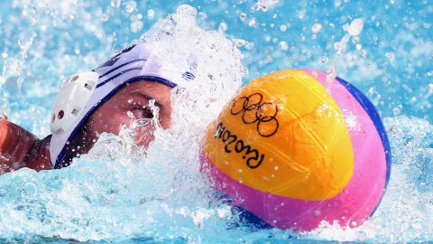 Angelos Vlachopoulos of Greece controls the ball against Japan during the men's water polo preliminary round group A match.