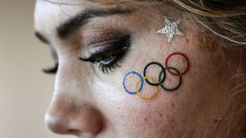 A volunteer wearing a temporary tattoo of the Olympic rings waits for the start of competition after the rowing event was delayed. Later the official governing body for world rowing confirmed that all races were canceled Sunday due to high winds and choppy waters at Lagoa.