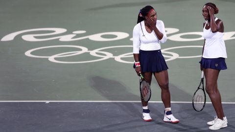 """Venus Williams talks with her sister Serena after losing a point against Lucie Safarova and Barbora Strycova of the Czech Republic. The Americans, defending their title, <a href=""""http://cnn.com/2016/08/07/tennis/serena-venus-williams-tennis-rio-2016/index.html"""" target=""""_blank"""">lost the first-round doubles match 6-3 6-4</a>."""