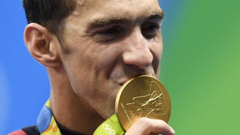 TOPSHOT - USA's Michael Phelps kisses his gold medal on the podium of the Men's 4x100m Freestyle Relay Final during the swimming event at the Rio 2016 Olympic Games at the Olympic Aquatics Stadium in Rio de Janeiro on August 7, 2016.   / AFP / GABRIEL BOUYS        (Photo credit should read GABRIEL BOUYS/AFP/Getty Images)