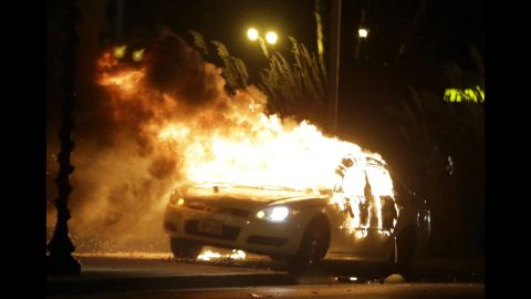 During the November 2014 protests following the grand jury's decision not to indict Wilson, some Ferguson businesses were looted and set on fire, along with police cars.