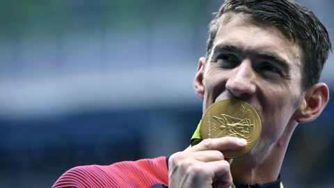 USA's Michael Phelps celebrates with his gold medal during the podium ceremony for the Men's 4x200m Freestyle Relay Final at the Rio 2016 Olympic Games on August 9.