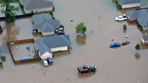 Rescue personnel and civilians team up to pull people from their homes along the Tangipahoa River on August 13.
