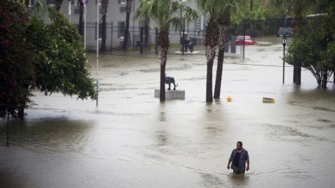 A resident wades through floodwaters at apartments near Louisiana State University in Baton Rouge.