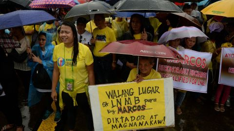 People braved the heavy but intermittent showers to voice their outrage over the decision to move the former dictator's body. Marcos ruled with an iron fist for two-and-a-half decades, and is accused of widespread corruption, overseeing torture and killings.