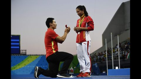"""China's Qin Kai <a href=""""http://www.cnn.com/2016/08/14/sport/china-diving-marriage-proposal-rio-2016-olympics/index.html"""" target=""""_blank"""">proposes to fellow diver He Zi</a> after she received silver in the 3-meter springboard on Sunday, August 14."""