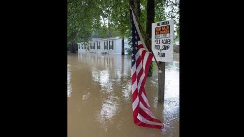An American flag hangs in floodwaters in Walker on August 15.