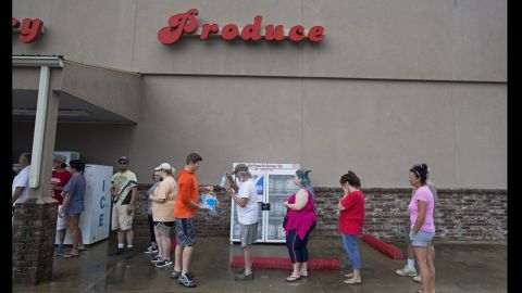 Eli Turnage hands out water to people waiting in line at Carter's Supermarket in Livingston on August 15.