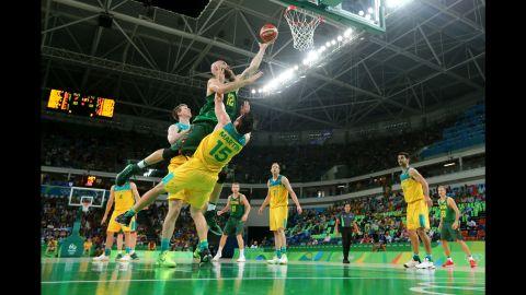 Antanas Kavaliauskas of Lithuania makes a layup over Australia's Damian Martin during a quarterfinal game. Australia won 90-64.