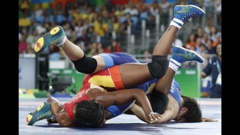 Brazilian freestyle wrestler Joice Silva, in red, competes against Kyrgyzstan's Aisuluu Tynybekova in a 58-kilogram (128-pound) qualification round.