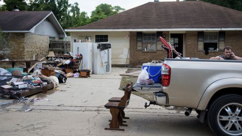 A man talks on his phone while helping salvage items from a house in Denham Springs on August 17.
