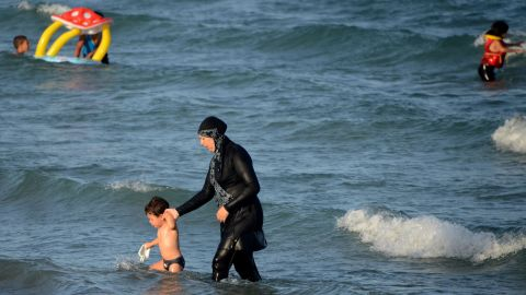 <strong>Burkini:</strong> The full-body swimsuit worn by Muslim women leaves only the face, hands and feet exposed. Here a woman in a burkini wades in the water with a child at Ghar El Melh beach in Tunisia.
