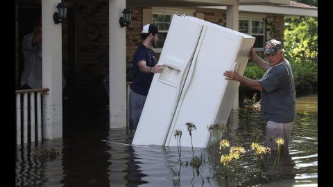 """Baron Leblanc, left, and George Snyder move a refrigerator out of George's flooded home in St. Amant on Thursday, August 18. More than 30,000 people have been rescued in southern Louisiana after heavy rains caused flooding. """"This is a major disaster,"""" Louisiana Gov. John Bel Edwards has said."""