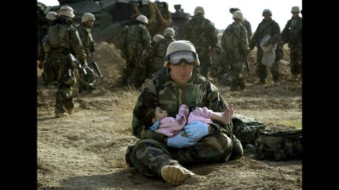 <strong>2003: Central Iraq</strong> -- A U.S. Navy hospital corpsman holds an Iraqi boy. Confused front-line crossfire ripped apart an Iraqi family. This moment of compassion was captured barely a year after the official start of the U.S.-led war in Iraq.