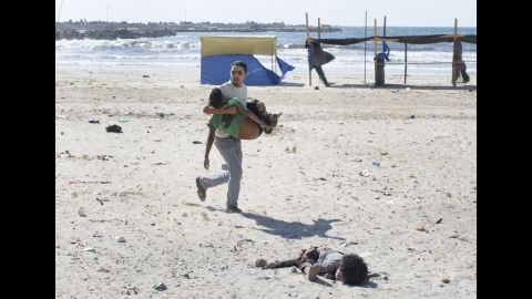 """<strong>2014: Gaza City </strong>-- A man carries a child as another lies dead after an Israeli airstrike on a Gaza City beach in July 2014. At least four boys, ages 9 to 11, were killed. The Israeli military investigated the tragedy and reported that the location of the attack was known to be a compound of Hamas police and naval forces. """"Tragically, in the wake of the incident it became clear that the outcome of the attack was the death of four children who had entered the military compound for reasons that remain unclear,"""" <a href=""""http://www.cnn.com/2015/06/11/middleeast/israel-gaza-beach-bombing/"""" target=""""_blank"""">the report stated.</a>"""