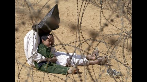 <strong>2003: Najaf, Iraq </strong>-- An Iraqi prisoner of war comforts his son in a POW holding zone. The emotional image won the 2003 World Press Photo award.