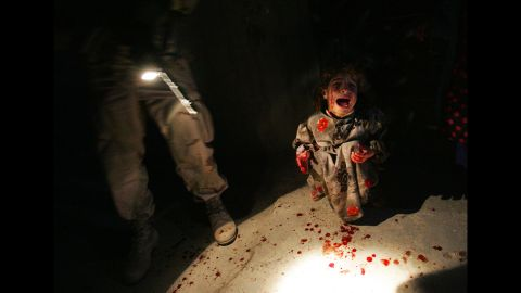 """<strong>2005: Tal Afar, Iraq</strong> -- In a time when truly resonant war photos were hard to come by due to the dangerous climate in Iraq, a photographer <a href=""""http://time.com/3808940/remembering-chris-hondros/"""" target=""""_blank"""" target=""""_blank"""">captured a truly wrenching moment.</a> The girl is Samar Hassan, screaming and spattered with blood after her parents were mistakenly killed and her brother was wounded by U.S. troops. The image was widely used to represent the true civilian cost of international conflict."""