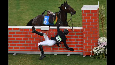 Jan Kuf of the Czech Republic falls from his horse in the show jumping portion of the modern pentathlon.
