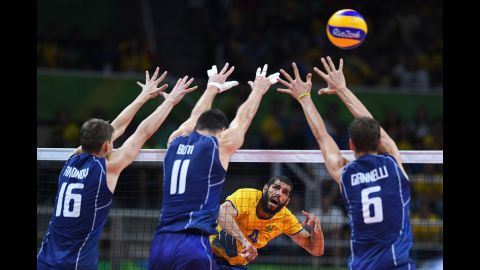 Brazilian volleyball player Wallace de Souza, in yellow, spikes the ball in the gold medal game against Italy. The Brazilians won.