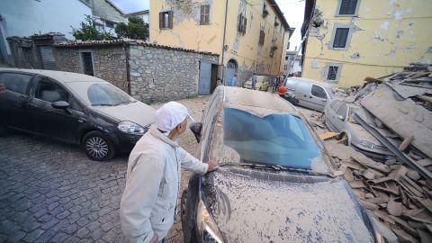 A man surveys damage near a dust-covered car in Amatrice on August 24.