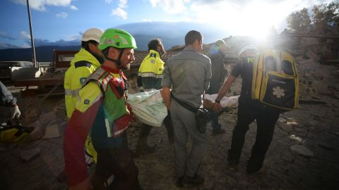 Rescuers carry a man through earthquake debris in Amatrice.