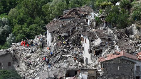 Search-and-rescue teams survey collapsed houses in Pescara del Tronto on August 24.