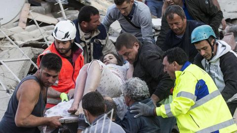 Rescuers help a woman from the rubble in Amatrice on August 24.