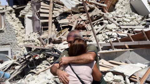 Two people hug each other next to damaged houses in Pescara del Tronto.