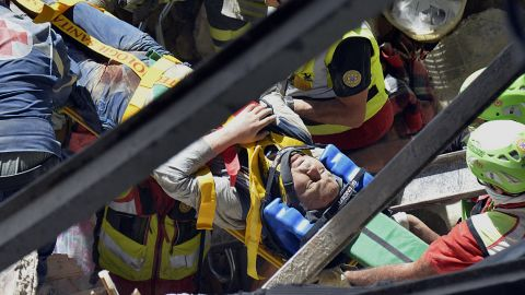 A man is pulled alive from the rubble.